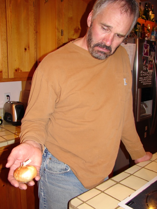 Randy sadly holding the very last onion before he adds it to the dinner.